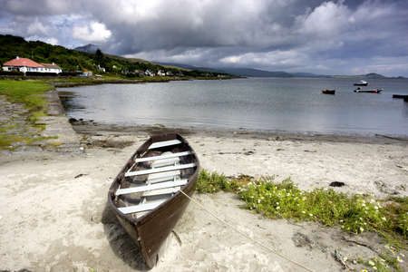 Islay, Scotland; An abandoned canoe by a beach