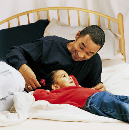 Father and little girl talking on a bed