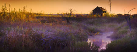 Abandoned shack at sunset near a creek