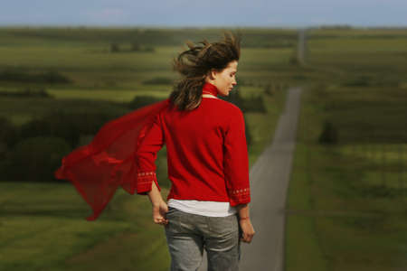 Woman walking on road surrounded by fields