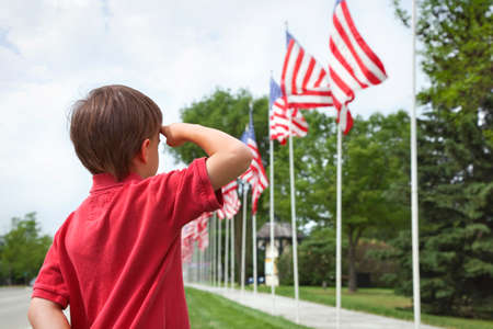 Foto per A young boy salutes the flags of a Memorial Day display along a small town street - Immagine Royalty Free