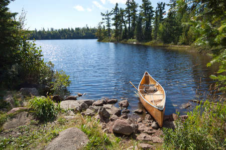 A yellow fisherman's canoe on a rocky shore of a northern Minnesota lake