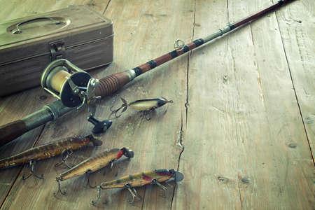 Photo pour Antique tackle box, bait-casting fishing rod, and lures on a grunge wood surface - image libre de droit