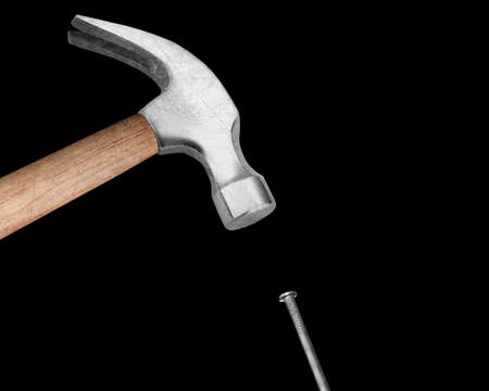 Hammer hitting a nail on black background.