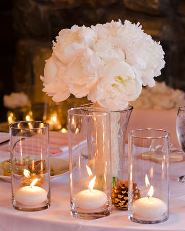 Photo for White and Pink Peony Wedding Bouquet in a Vase Accented by Candles and Pine Cones on a Table - Royalty Free Image