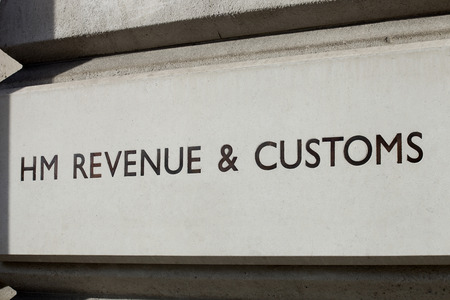 A carved sign for HM Revenue & Customs, the British Tax office.