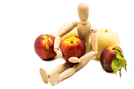 wooden man puppet sitting hugging a nectarine on white background