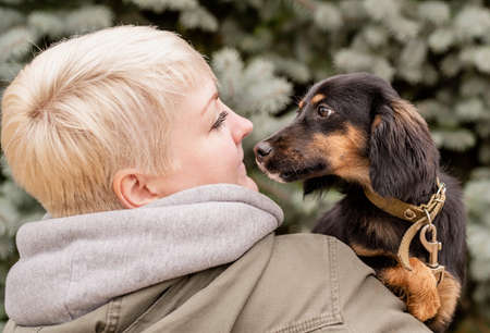 Photo pour Woman hugging her dog on fir tree background outdoors - image libre de droit