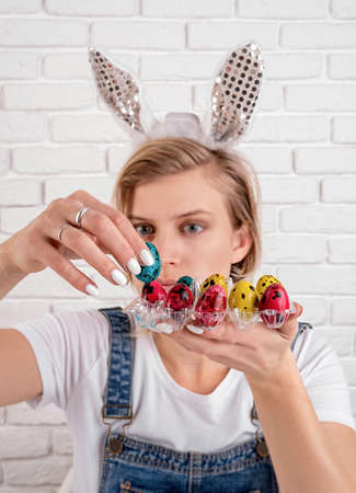 Photo pour Easter holiday concept. Young funny woman in bunny ears putting a colored quail egg into the plastic holder - image libre de droit
