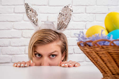Photo pour Easter holiday concept. Blond woman with bunny ears looking at the basket with Easter colored eggs on white brick background - image libre de droit