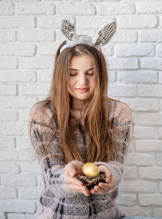 Photo pour Easter concept. Cute woman in bunny ears holding a small nest with an egg in her hand - image libre de droit