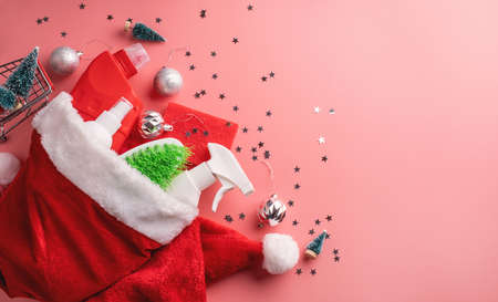 Photo for Christmas cleaning. Christmas shopping. Cleaning tools and Christmas decorations in santa hat top view flat lay on pink background with copy space - Royalty Free Image