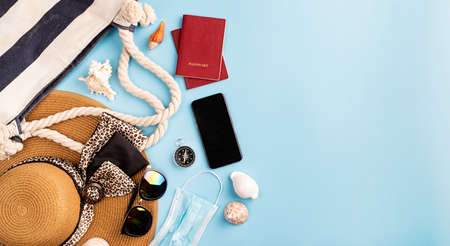 Foto de Travel and adventure.Flat lay traveling objects with summer hat, smartphone, passport, sunglasses and compass on blue background with copy space - Imagen libre de derechos
