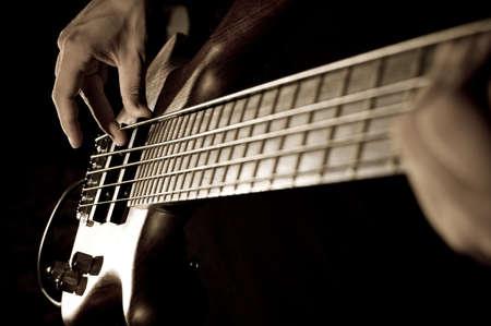 hands of a boy playing bass guitar