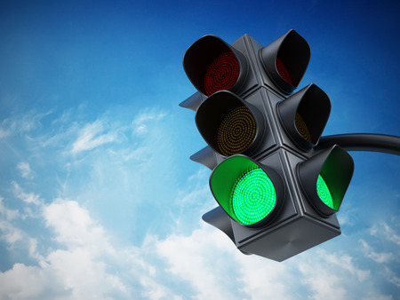 Green traffic light against blue sky.