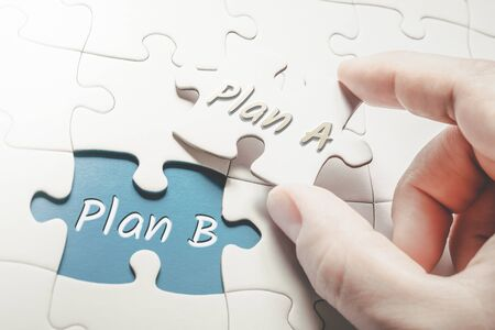 Photo for Plan A and Plan B In Missing Piece Jigsaw Puzzle, Two Fingers Holding Plan A Piece - Royalty Free Image