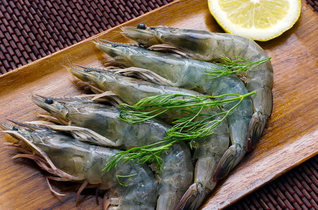 Fresh Shrimps with herbs and lemon on wooden plate