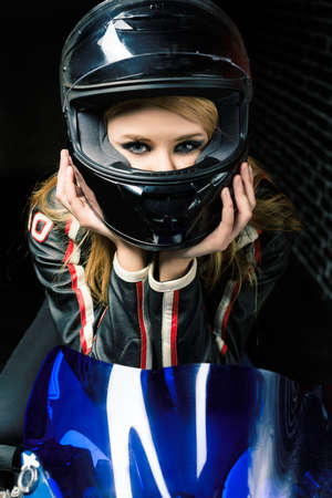 Moto close up of young girl in black helmet. Retouched image.