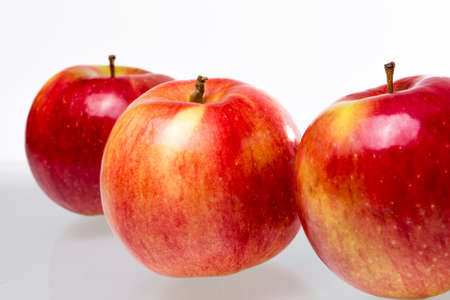 Three red apples in perspective on a white backgroundの写真素材