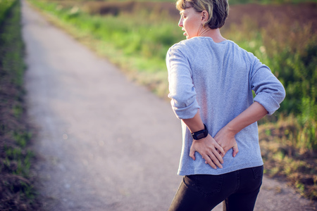 People, healthcare and problem concept - woman suffering from pain in back or reins outdoor