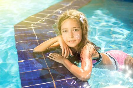 Photo pour Kid girl with sun protection cream on her skin spends time in the pool. Children, summer, holiday and healthcare concept - image libre de droit