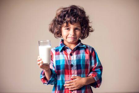 Photo pour Kid boy with stomach pain holding a glass of milk. Dairy Intolerant person. Lactose intolerance, health care concept. - image libre de droit