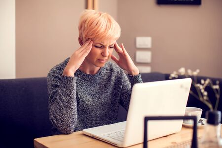 Photo pour Stressed woman working with laptop feeling headache. People, health care and technology concept - image libre de droit