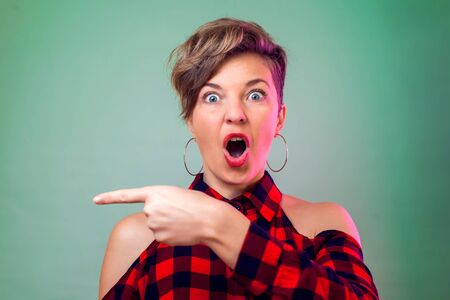 Photo pour People and emotions - surprised young woman show with finger on something - image libre de droit