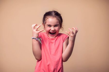A portrait of shouting evil kid girl. Children and emotions concept