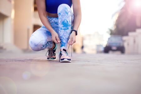 Woman tying shoelaces while training outdoor. Close up. People, fitness and lifestyle concept