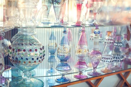 A lot of beautiful empty arabic style glass bottles for perfume in the shop behind the glass window