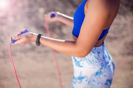 Woman training with jump rope outdoor. Close up. People, fitness and healthcare concept
