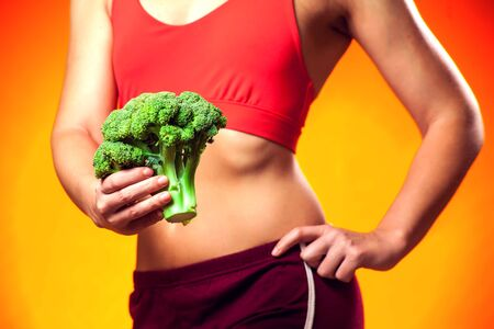 Photo for Woman in sportswear holding broccoli. People, fitness and dieting concept - Royalty Free Image