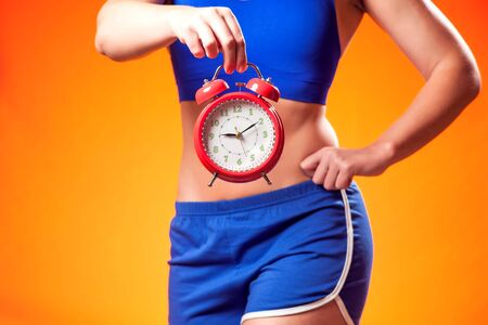 Photo pour Woman in sportswear holding alarm clock. People, fitness and dieting concept - image libre de droit