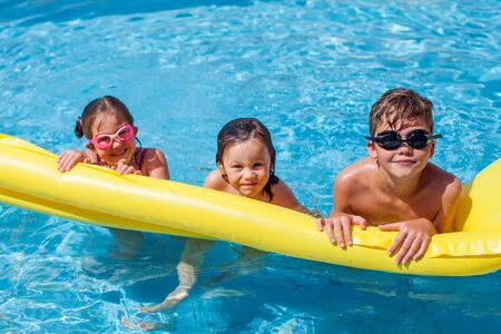 Photo pour Kids playing in the swimming pool. Childhood, summer and holiday concept - image libre de droit