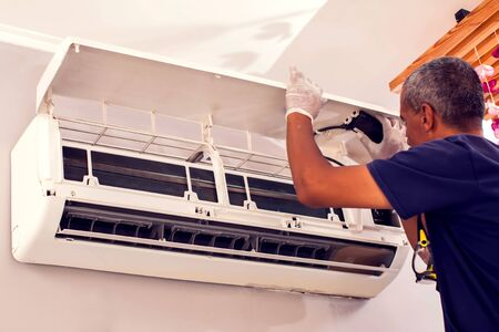 Photo pour Man worker fixing air conditioning on the wall. Professional service - image libre de droit