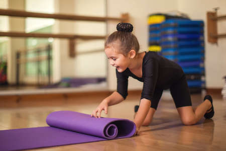 Photo for Kid girl at gymnastic class doing exercises. Children and sport concept - Royalty Free Image