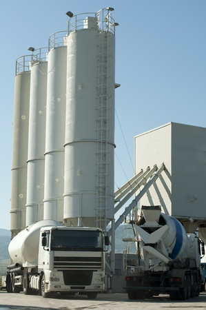 Cement factory and two white trucks loading cement