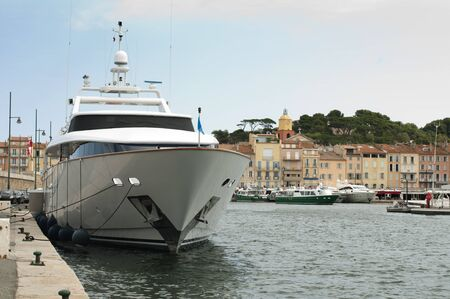 Anchored Yacht in St. Tropez. Ancient buildings on the background.
