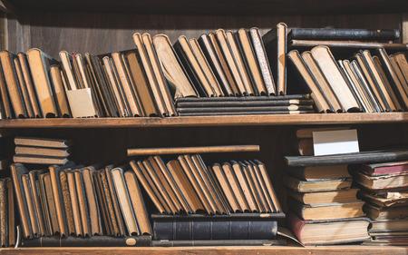 Photo pour Old books in a vintage library shelfs - image libre de droit