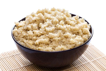 Cooked organic quinoa in brown bowl on white background