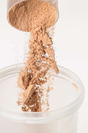Scoop of chocolate whey isolate protein tossed into plastic white shaker, with focus on the protein in the scoop and falling protein blurred