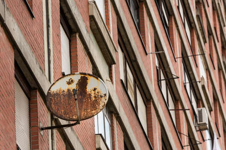 Old rusty TV receiver satellite dish installed on residential building window, symbol of old technology, as opposed to the modern wired and optical cable TV systems