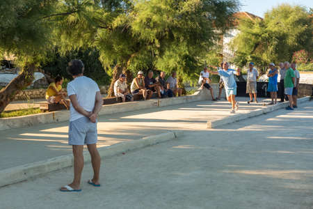 VELI IZ, CROATIA - AUGUST 23, 2014: Group of senior citizens playing game of boules (petanque, bocce) on the playing field. Boules is a popular recreational activity of senior citizens in Dalmatia region of Croatia.