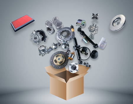 Many spare parts flying out of the box on grey background