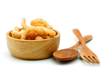 Photo for Pork snack or Pork scratching leather lean pork fried crispy and blistered in wood bowl with spoon and fork isoloated on white background. Thai food, Close-up - Royalty Free Image