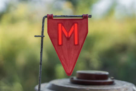 Photo pour Red plastic minefield pointer with a red glowing letter M with a mine in the background. - image libre de droit