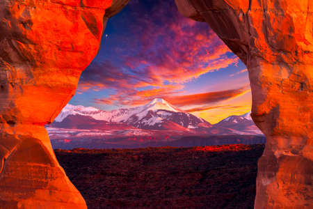 La Sal Mountains, as seen through Delicate Arch, on a colorful late afternoon in Arches National Park, Utah