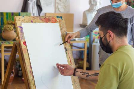 Foto de teacher helping student in art scholl, student with protective mask drawing picture - Imagen libre de derechos