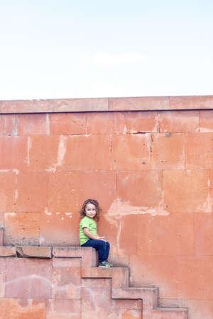 Foto für portrait of a little long hair boy near the wall on stairs - Lizenzfreies Bild